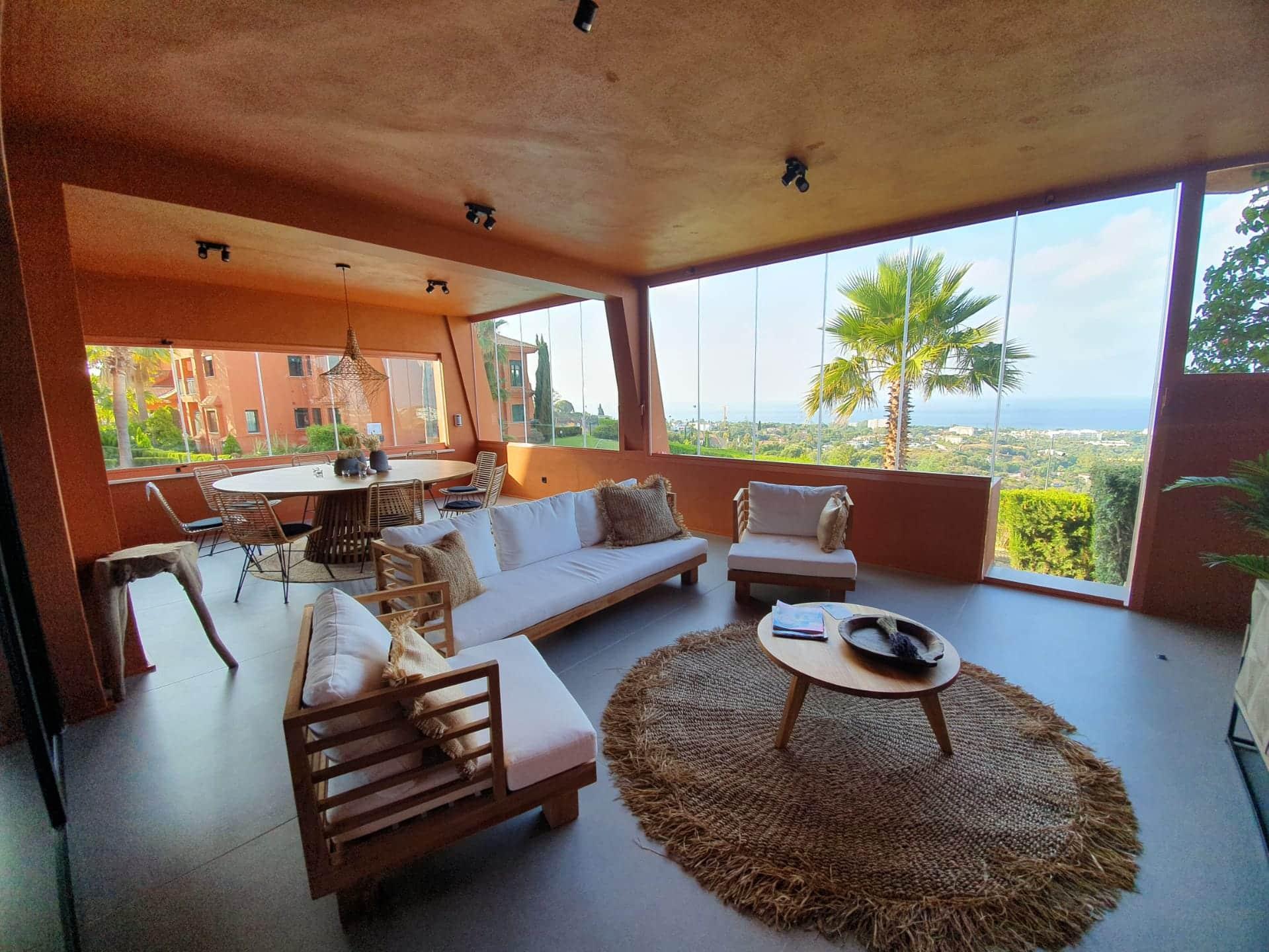 Terraza exterior cubierta y cerrada con cortina de vidrio reforma piso Marbella, decoración ibizenca